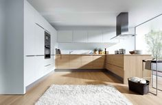 Modern kitchen design. Light oak fronts and worktop with white wall units