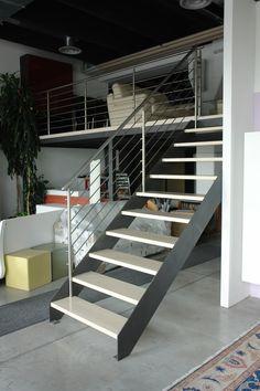 Scala a giorno con doppia struttura laterale in ferro, gradini in massello di faggio e barriera un lato in acciaio inox.