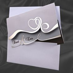 Graue Hochzeitskarte mit verschlungenem Herz in Gold.