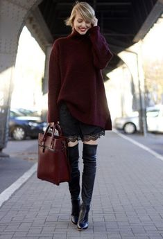 Woman wearing an oversized sweater with a short skirt and black knee high boots
