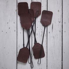 These luxurious fly swatters have tough stainless steel handles and brown leather housefly whacking flaps at the end.