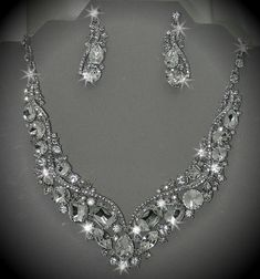 Rhinestone Bridal Bib Statement Necklace and Earrings Set..Available in additional colors... Sale Items... Hand Embellished by designer Jane Robinson...This Bridal Bib Necklace and Earring Set is a Made to Order item with Free Stud Post Earrings using Austrian Crystal Rhinestone Components... ~ High Quality... Necklace Size : 13 + 6 L Charm Size : 1 1/2 L Earring Size : 2 L ~ Gorgeous wedding accessory for todays modern vintage looks... ~ Perfect for wedding wear - brides... ~ Free Rhin...
