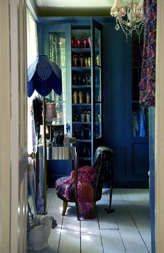 Feminine shabby chic doesn't have to be delicate. The intense inky blue used on the cupboard and echoed in the standard lamp shade and upholstered chair gives depth and drama to this shabby chic boudoir replete with chandelier. TS