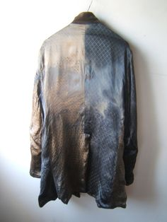 ((Geoffrey B. Small))  What an eccentric and strange coat.  I love coats that are too big for me. I have long worn men's coats and jackets, as they envelop me and hide me.  This has a potent mystery to it, this piece.  I would wear this. As a smaller person, I love being hidden......