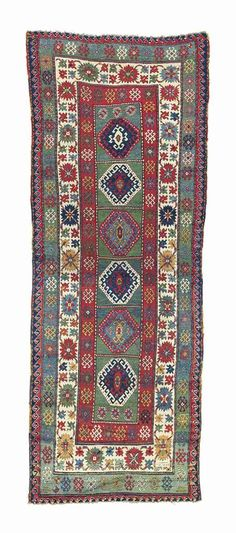 KAZAK LONG RUG  SOUTH CAUCASUS, DATED AH 1288/1871 AD    10ft.11in. x 4ft. (330cm. x 122cm.)