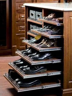 Traditional dark stained closet features a closet island fitted with stacked pull-out shoe shelves.