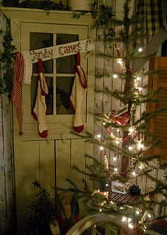 Prim Stockings hanging in a row...old white corner cupboard, candy cane sign, and primitive Christmas tree...