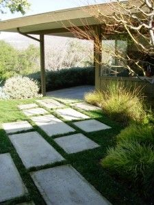 This pathway cuts in diagonally to the front door and uses rectangular and square poured-in-place concrete pavers.