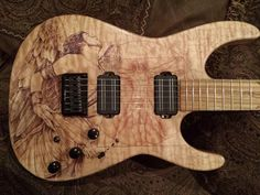 June 2014 Guitar of the Month Contest - Kuro Uma: Alder body with Unique Choice Quilt Maple top. Customizations include: Dyed Icarus and Vetruvian man with other DaVinci writing, Ebony knobs and black hardware, and more!