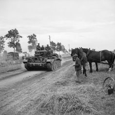 British medium cruiser tanks Mk.VIII Cromwell from part of the 7th armored division passes by a local resident in Normandy. On 30 July 1944.