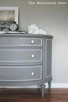 A grey demi lune dresser with white accents. Buffet colors?