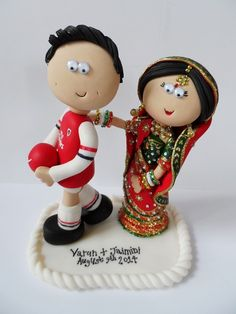 Arsenal football loving Groom with his lovely Bride who doesn't love Arsenal! I can make figurines in any outfits or poses you want, handmade from scratch and personalised to look like the people getting married. NOT EDIBLE, last forever as a great keepsake of the big day. I send my work anywhere in the World. Something like this is £149.99 for the couple, £9.99 for a base (they don't need one to stand).