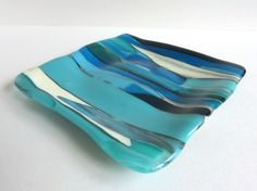 This beautiful handmade fused glass plate in abstract stripes of turquoise, black and french vanilla would make a great additional to your home decor.