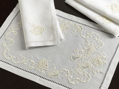 Sferra Liliana Table Linens - Formal flowers. SFERRA's Italian Classico linen plays host to embroidered Ivory blooms and scrolls that follow an elaborate hand-drawn hemstitched border on tablecloths and napkins. A unique and timeless design that will delight and inspire. Made in Italy. White linen with Ivory embroidery.