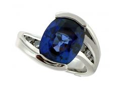 Stunning Custom Oval Blue Sapphire Ring set in a Swirled White Gold Design with Round Side Diamonds from Miner's North!