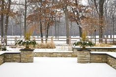Snowy garden - stone wall with evergreen filled urns - design by The Garden Consultants, Inc. - Photo by Linda Oyama Bryan