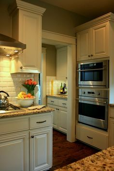 This is a lot what my kitchen will look like.  Granite countertop is similar, cabinets similar in both style and color, stainless steel appliances (no double oven, though), dark floor.  I think we should go with that same look for the wall behind the stove.