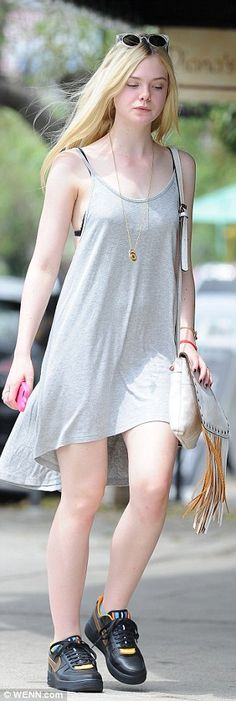 Cool and casual: Elle completed her look with a pair of sunglasses, a fringe leather purse...