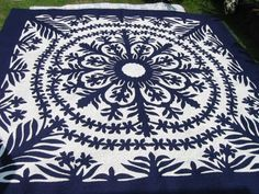 HAWAIIAN QUILT- The design is pinned down on the background fabric, then basted to hold it in place. Using the same color thread as the design, slip stitch 1/8 inch under all around the design. Traditional quilting on top of that. Photo from the blog, An American Housewife.