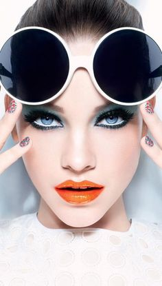 Giant retro circular sunglasses, with blue eyes and smoky shadow and pretty orange-red lips.