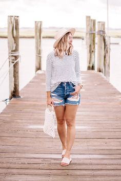 What to wear on Labor Day weekend: classic and easy Labor Day outfit inspiration for one last summer outfit while there's still time.  Classic summer outfit/classic beach outfit/classic vacation outfit/nautical outfit/nautical style/classic beach style/classic vacation style/end of summer outfit/late summer outfit or Labor Day outfit with denim cut offs, a navy striped t-shirt (long sleeve t-shirt), net bag, straw boater hat, straw hat and beige sandals (beige woven sandals).