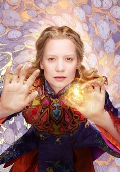 Mia Wasikowska, as Alice from Disney's Alice Through the Looking Glass (2016). Those golden orbs look to be in all of character images. From IMBD.