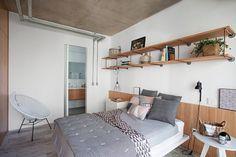 Desenhada pelo escritório Casa 100 Arquitetura, a cama branca, com roupa da Tri.co Decor, tem atrás um painel de carvalho americano (Foto: Gui Morelli / Divulgação)
