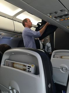 June 21, 2016: Prince William stows his own bag today as he flies Club World Class back from Lyon to Heathrow on Tuesday morning after England's disappointing match in St. Etienne. The 34-year-old Football Association president was whisked onto the British Airways flight from Lyon to Heathrow just minutes before take-off this morning. Then Prince William promptly nodded off. ~ Photo by MailOnline.