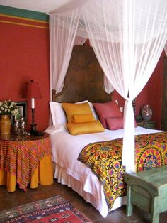 A subdued version of tangerine comes in on the bed with the throw, pillows and table skirt. This bohemian style bedroom gives off a global feel.