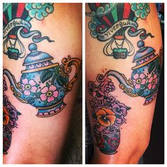 Teapot and teacup tattoo with pansies pouring out of the teapot. American traditional.
