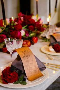 This table setting features classic roses with a gold setting template and a deep plum napkin.
