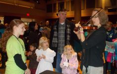 Richmond Symphony Youth volunteer at Instrument Petting Zoo  with a happy family!