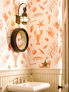 Designer Carrie Miller had fun with the nautical theme in this powder room. She paired red-and-white wallpaper with a lobster motif with a porthole mirror and lantern light fixture. Not a fan of the paper but I love the light and mirror! Nantucket Cottage, Beach Cottage Style, Coastal Cottage, Coastal Style, Coastal Decor, Seaside Decor, Seaside Inn, Maine Cottage, Coastal Homes