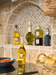 BackSplash-Creative Cutouts in the kitchen - With handsome tiles and striking bottles, the cooktop niche boosts storage and style. The wall becomes the focal point of the kitchen and the recess provides an easy way to store cooking supplies. Kitchen Ikea, New Kitchen, Kitchen Tips, Kitchen Utensils, Toscana Italia, Cooking Supplies, Tuscan House, Mediterranean Home Decor, Tuscan Decorating