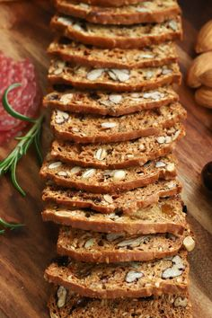Overhead photo of a loaf of Copycat Rosemary Pecan Raincoast Crackers cut in thin slices on a wood appetizer board.