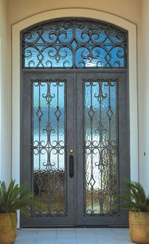 Moroccan style wood with iron front door with matching transom.