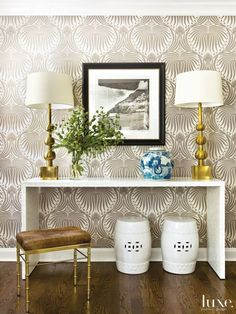 Farrow & Ball's Lotus wallpaper covers the foyer walls. Brass touches, including Vaughan table lamps and a bench from Jayson Home, complement an Oly waterfall console and garden stools from One Kings Lane. The owners purchased the black-and-white photograph in Italy.