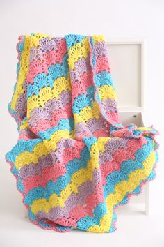 Bright and festive springtime shades join together to form this full-sized afghan that's sure to add some warmth and sunshine to any room of the house. This throw features delicate shell stitches throughout to add some openness to the design.