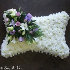 Traditional pillow-shaped tribute, based in white chrysanthemums and dressed with a corsage. You can chose the colour scheme of your corsage below.Size Shown is StandardWe require four working days notice for this piece.Please let us know the time and date of the funeral and the name of the deceased - you can add this in the notes box at checkout.