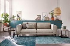 Woonkamer met lichtgrijs NOCKEBY bankstel, bruine salontafels en blauwe vloerkleden