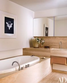 In the travertine-lined master bath, a Robert Mapplethorpe photograph is displayed above the tub, which is equipped with Vola fittings | archdigest.com