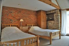 This beautiful twin room with large windows, exposed brickwork and stone walls plus dressing table is part of Spring Cottage.                      #Cotswolds #holiday #rental