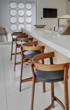 Kitchen. The kitchen features vintage european barstools and an outdoor atrium with a wall sculpture of repurposed concrete wall medallions from a mid century bank building. #interiordesign #kitchen #kitchendesign