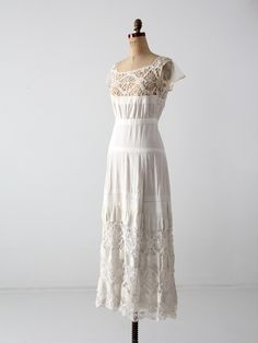 circa early 20th century This is a stunning late Victorian era white dress underpinning. The white cotton dress features a crochet lace bodice with mesh lace cap sleeves. The petticoat skirt is tiered