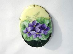 Victorian porcelain brooch is hand painted with a spray of vibrant purple violets