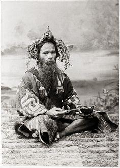 Ainu man sitting at the ground with ikupasuy (prayer stick), 1901 by Bashford Dean