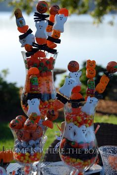 Arrange various Halloween Treats in different size vases and thread marshmallow ghost/candies on sticks to help finish the centerpieces. Super easy and super cute! You could even have several black/orange helium balloons attached to the sticks as well.