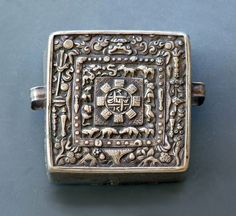 ⊕Hover to zoom  Move your mouse over image                Calender Gau  Size:  7 x 7cm  Region:  Tibet  Type:  Gau for men  Age/Period:  19th century  Material:  Silver, backside iron