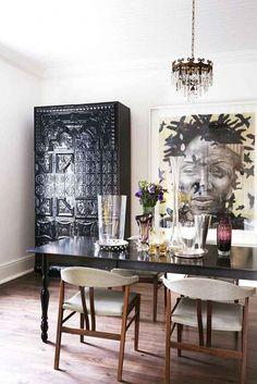 A collected dining space with antique pieces, artwork, and large glass vases on table