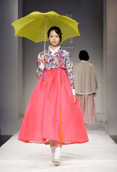 "A Model walks down the catwalk during the South Korean Traditional Costume 'HanBok' fashion show on October 21, 2011 in Seoul, South Korea. Hanbok is the traditional Korean dress. It is often characterized by vibrant colors and simple lines without pockets. Although the term literally means ""Korean clothing"", hanbok today often refers specifically to hanbok of Joseon Dynasty and is worn as semi-formal or formal wear during traditional festivals and celebrations."